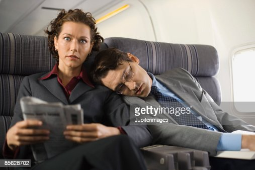Uncomfortable passengers sleeping and reading on airplane