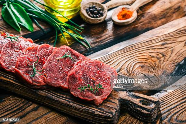 Uncooked meat on rustic wood