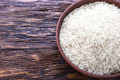 traditional food, uncooked rice in a bowl on a wooden background