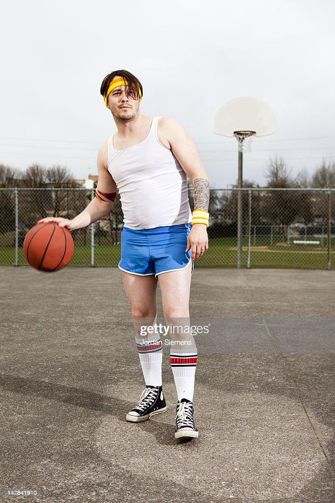Uncoordinated man playing basketball. : Stock Photo