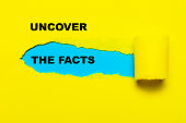 uncover the facts message on torn paper.