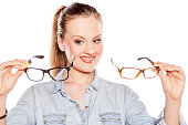 smiling young blonde compares two pair of glasses
