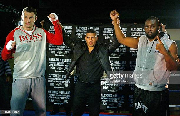 Undefeated 140lb prospect Miguel Cotto raises the arms of WBC Heavyweight Champion Vitali Klitschko and challenger Danny Williams pose after an open...