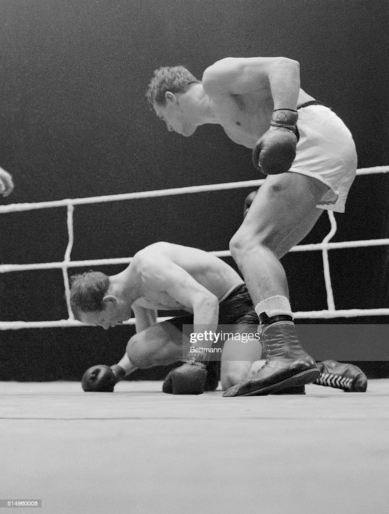 Undefeated middleweight champion of Germany Gustav 'Bubi' Scholz towers over fallen opponent Wille Armstrong of Scotland in their scheduled ten...