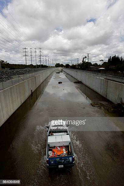 – – Under a brilliant white cloud filled Monday sky an Orange County Maintenance vehicle drives North through very shallow storm water in the...