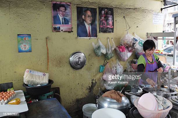 Under a picture of Thailand's king a woman cooks food on the street at the entrance of the Ban Batt community alleyway on October 25 2012 in Bangkok...