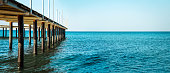 Under a pier, clear turquoise water of the Caribbean Sea.