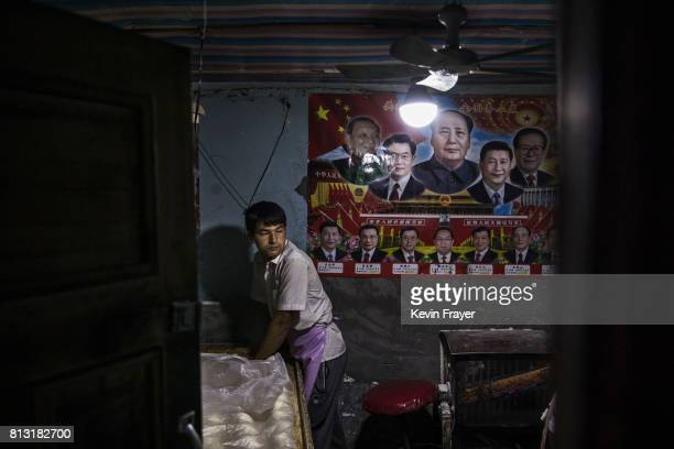 Under a poster showing Chinese leaders including the late Mao Zedong and the present President Xi Jinping an ethnic Uyghur man makes bread at a local...