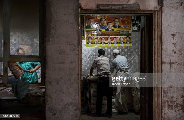 Under a poster showing Chinese leaders including the late Mao Zedong and the present President Xi Jinping ethnic Uyghur men make bread at a local...