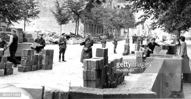 Under armed guards East German workers unload and cement concrete blocks to build the Berlin Wall Berlin Germany 1961