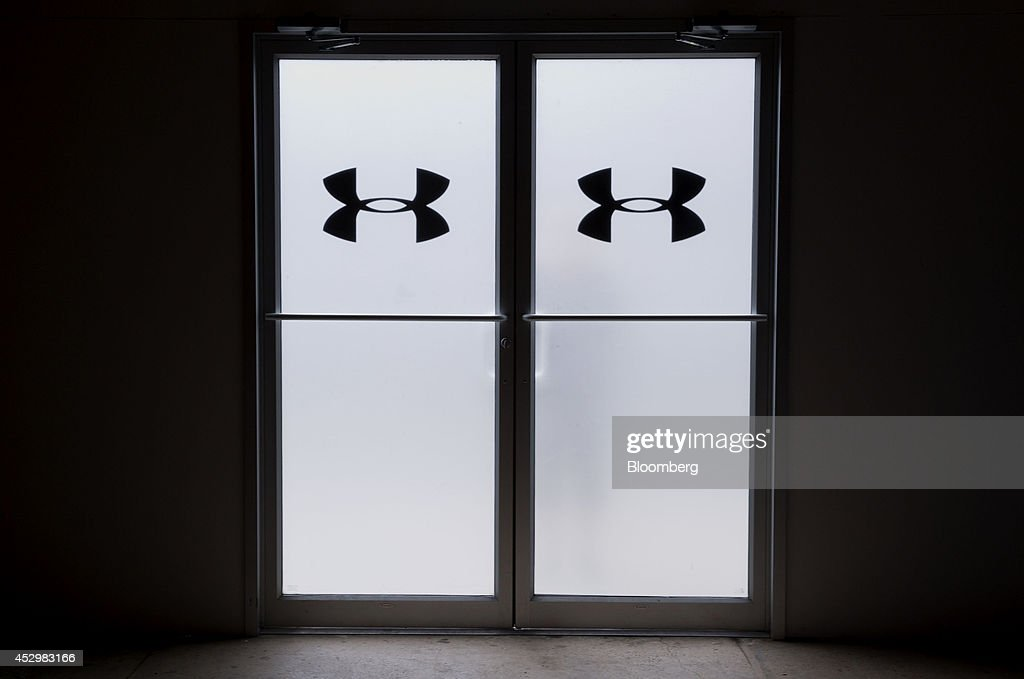 Under Armour Inc. signage is displayed on doors during a news conference in New York, U.S., on Thursday, July 31, 2014. Under Armour Inc., the maker of compression T-shirts and other athletic apparel, launched its most expansive global women's marketing campaign. Photographer: Jin Lee/Bloomberg via Getty Images