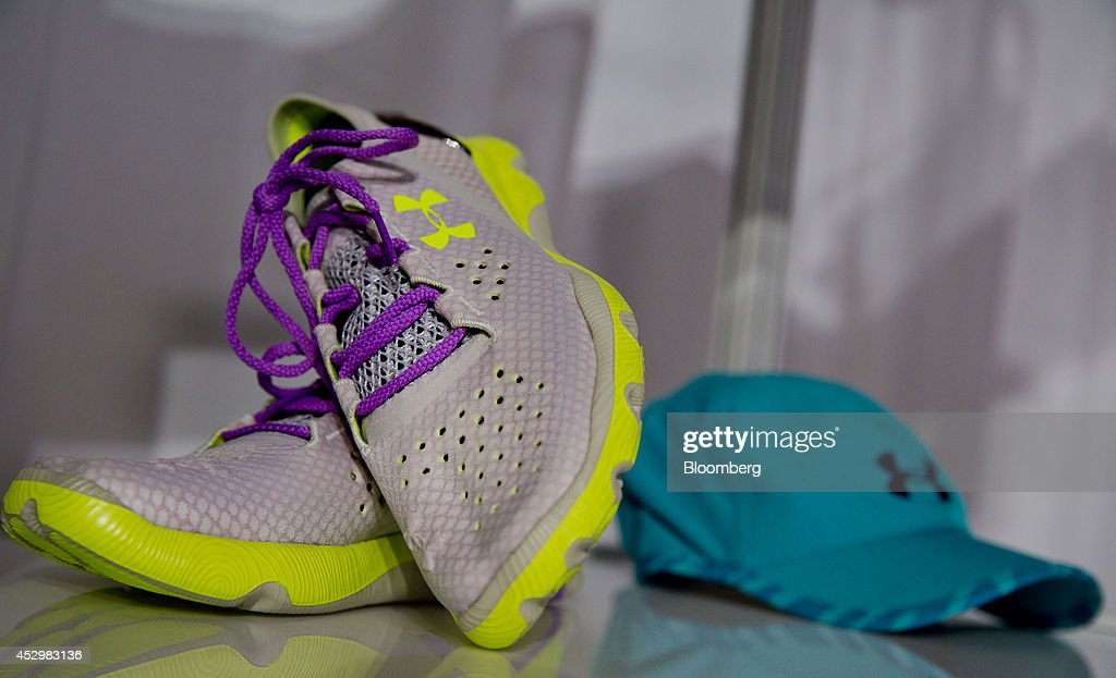 Under Armour Inc. women's shoes and a hat are displayed during a news conference in New York, U.S., on Thursday, July 31, 2014. Under Armour Inc., the maker of compression T-shirts and other athletic apparel, launched its most expansive global women's marketing campaign. Photographer: Jin Lee/Bloomberg via Getty Images