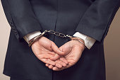 Business man in a suit with handcuffs, under arrest for corruption and bribery. Selective focus