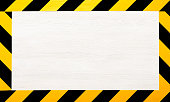 Under construction concept background. Warning tape frame on white wooden surface background with copy space.