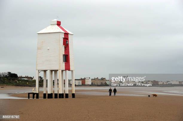 Under dark grey clouds on the first day of the Easter Bank Holiday weekend as owners walk their dogs along the beach near Low Lighthouse at...