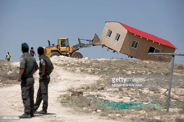 Under heavy police guard an Israeli authority bulldozer demolishes an illegal house in the illegal West Bank settlement of Maale Rehavam southeast of...
