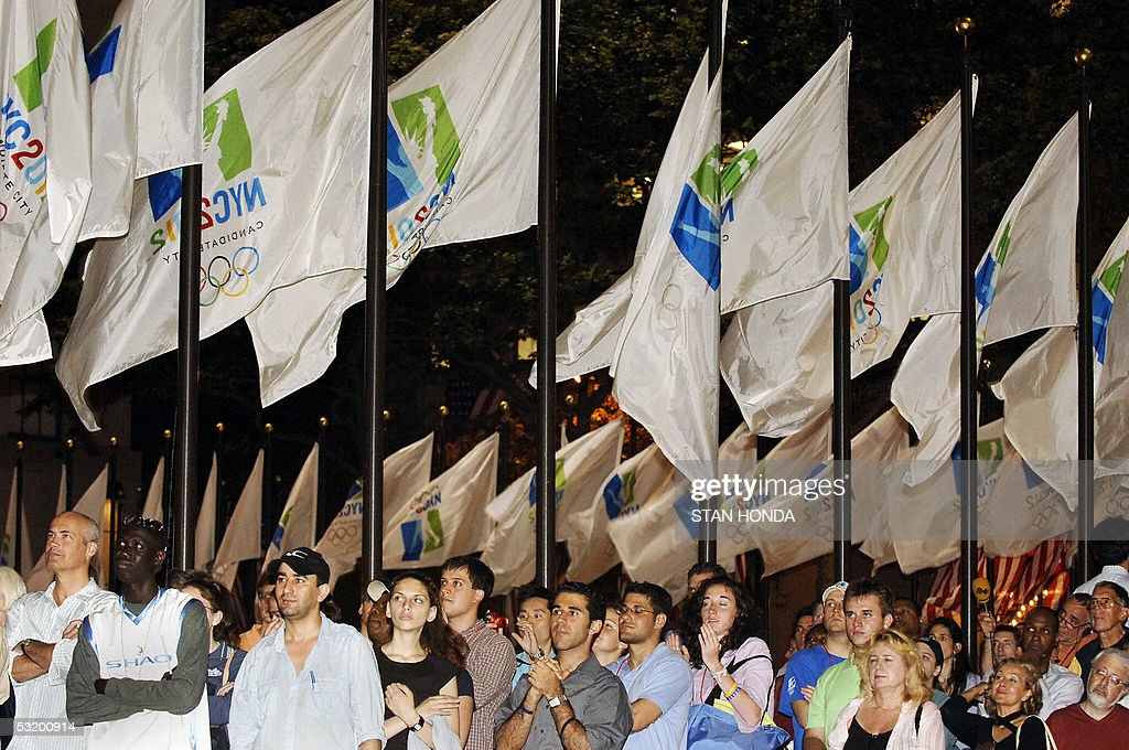 Under NYC2012 flags in New York's Rockefeller Plaza people watch the New York City Olympic bid committee present their proposal to host the 2012...