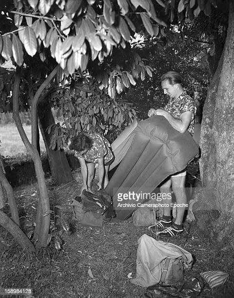 Under some trees a couple inflate an air mattress outside their tent Padova Italy 1950