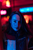 Portrait of a young woman illuminated by neon city lights