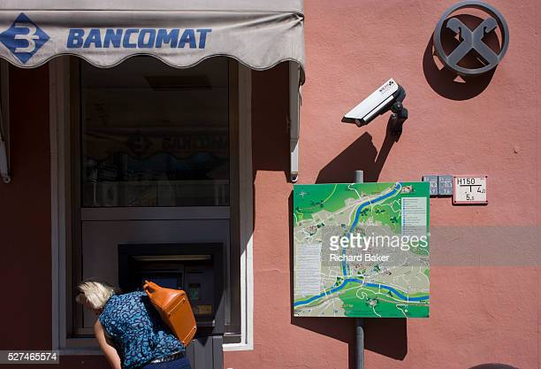 Under the gaze of CCTV a customer uses a Bancomat cash dispenser in the northern Italian south Tyrolean city of BozenBolzano The woman leans over to...