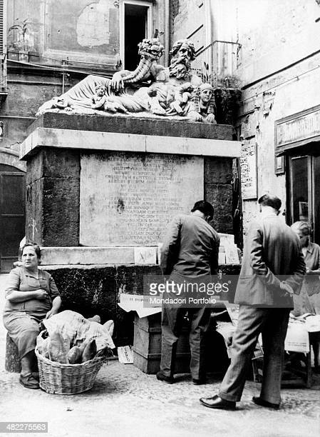 Under the Nile statue in the old town centre of Naples an elderly woman sitting near a basket full of bread and some men looking at some newspapers...