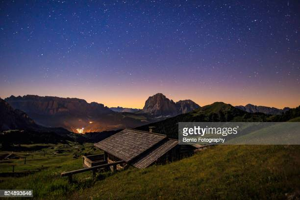 Under the starry sky with a small house in Seceda, Italy