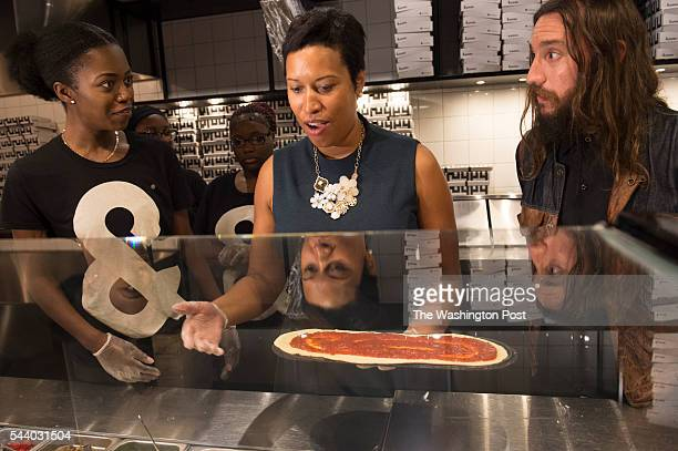 Under the watchful eyes of Kyonna Hicks left and Pizza owner Mike Lastoria at right Washington DC Mayor Muriel Bowser tries her hand at pizza making...