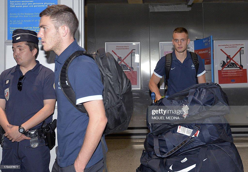 Under-20 French team goalkeeper Maxime Dupe (R) arrives with teammates at the Roissy-Charles-de-Gaulle airport, on July 14, 2013, a day after defeating Uruguay during their FIFA Under 20 World Cup final football match in Istanbul. France won the title after defeating Uruguay 4-1 on penalties following a goalless draw.
