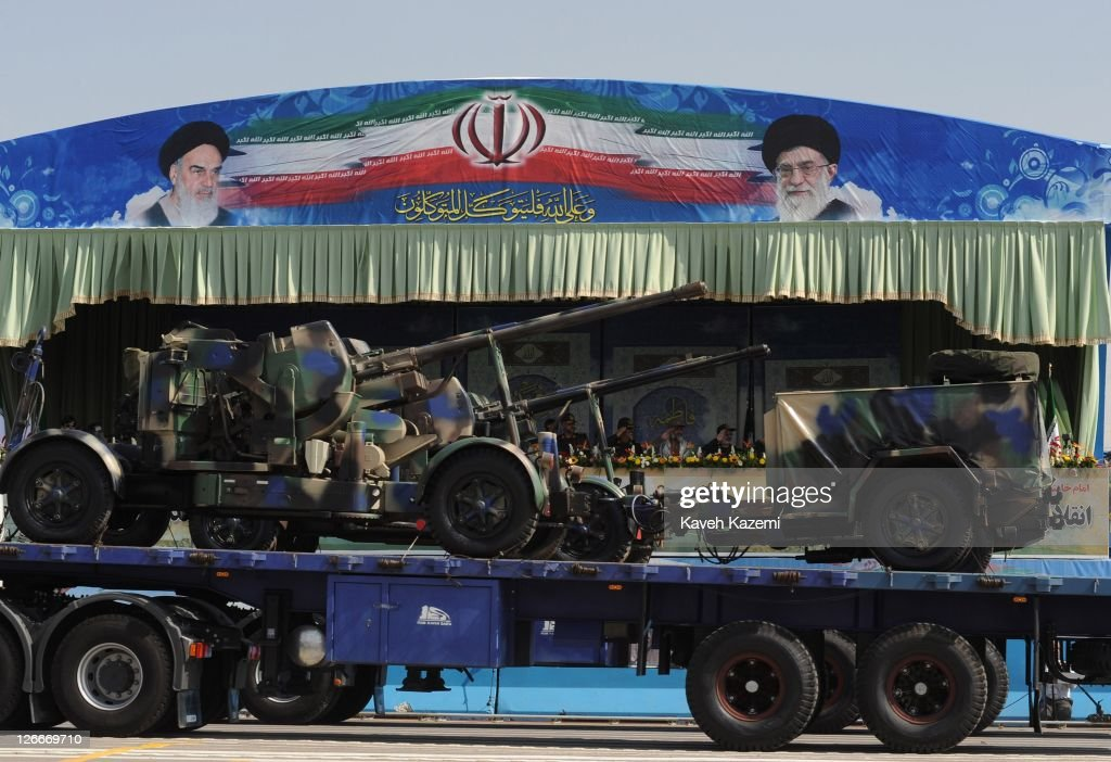 Undera banner displaying Ayatollah Khomeini (L) late leader of Iran and Ayatollah Ali Khamenei the present leader, military commanders watch military armaments transported on a vehicle during a military parade commemorating the 31st anniversary of Iran-Iraq war on September 22, 2011 in Tehran, Iran. Iran is holding military parades in Tehran and other parts of the country on the first day of the Sacred Defence Week. Tehran's parade began to the north of Imam Khomeini's mausoleum providing the army, Islamic Revolution Guards Corps, Law Enforcement Force and Basij with an opportunity to display their state of military preparedness, in which armaments and indigenously built military equipment including Shahab missiles, unmanned aircrafts, Zulfaqar tanks, and a variety of rapid fire machine guns were showcased.