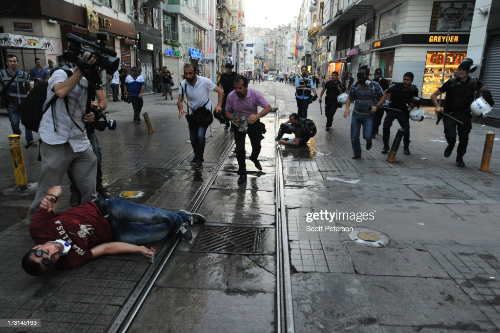 Undercover police move to arrest a protestor after tripping him to the ground, as Turkish police battle anti-government protestors along the Istiklal shopping street near Taksim Square on July 8, 2013 in Istanbul, Turkey. The protests began in late May over the Gezi Park redevelopment project and saving the park trees adjacent to Taksim Square but swiftly turned into a protest aimed at Prime Minister Recep Tayyip Erdogan and what protestors call his increasingly authoritarian rule. The protest spread to dozens of cities in Turkey, in secular anger against Mr. Erdogan and his Islam-rooted Justice and Development Party (AKP).