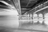Long exposure on the underside of Bournemouth pier in black & white with the tide coming in.