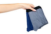 Underpants and clothing for kids with hand isolated on white background.
