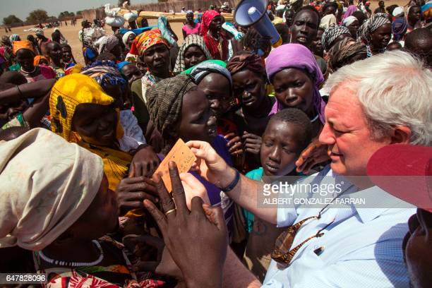 UN UnderSecretary General for Humanitarian Affairs and Emergency Relief Coordinator Stephen O'Brien checks a beneficiary's ration card for a food...