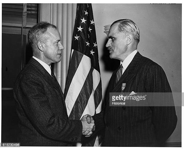 US Undersecretary of War Robert P Patterson and nuclear physicist Arthur Holly Compton recipient of the 1927 Nobel Prize in Physics shake hands
