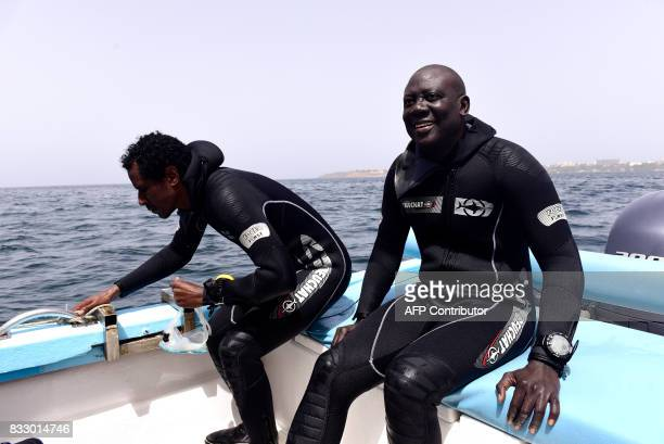 Underwater archaeologist Ibrahima Thiaw and a team member work on a boat during a diving expedition to find traces of slave shipwrecks on May 16 2017...