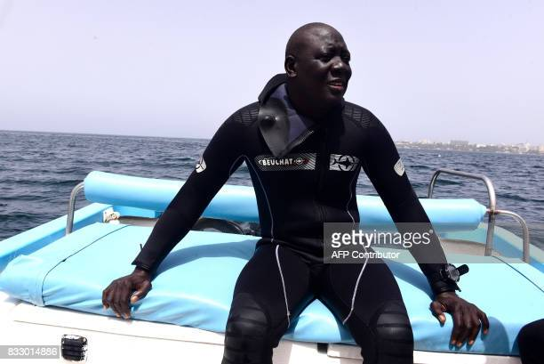 Underwater archaeologist Ibrahima Thiaw waits on a boat during a diving expedition to find traces of slave shipwrecks on May 16 2017 off the island...