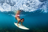Sportive girl in bikini in action. Surfer with surf board dive underwater under breaking ocean wave. Healthy lifestyle. Water sport, swim, extreme surfing in adventure camp on summer beach vacation