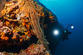 Underwater photographer  Scuba divers photographing  Explore reef   Old fishing net