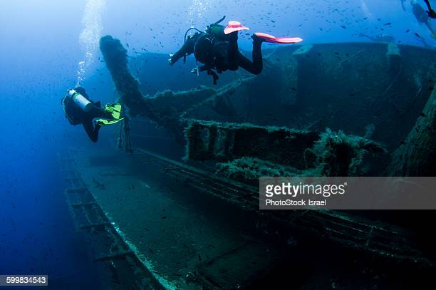 Underwater rear view of divers investigating MS Zenobia shipwreck, Larnaca, Cyprus