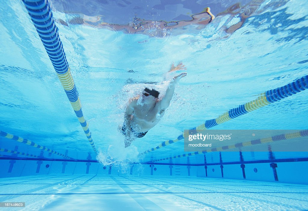 Underwater shot of young male athlete swimming in pool : Stock Photo