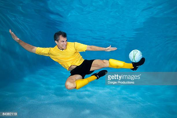 Underwater soccer player kicking a ball
