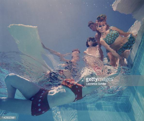 Underwater view looking up at a group of swimwear models in and around a swimming pool Palm Springs California 1964 The photo was taken for an issue...
