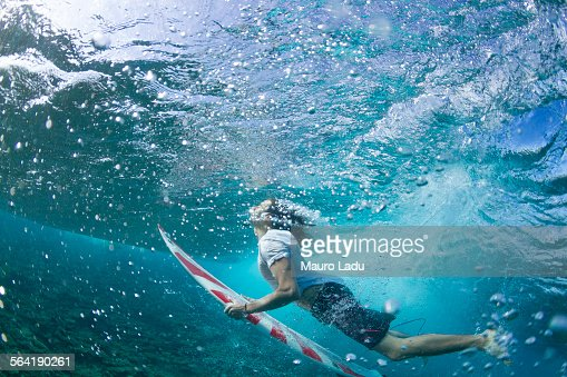 Underwater view of a surfer duck diving under a wave