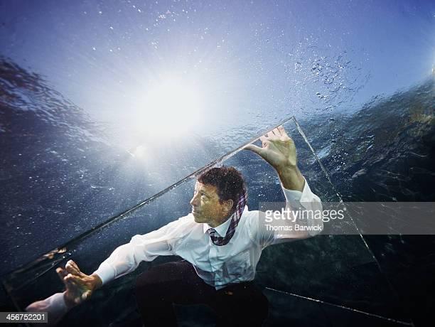 Underwater view of businessman in glass box