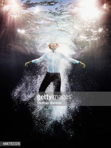 Underwater view of businesswoman treading water