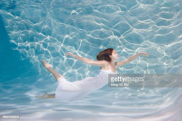 Underwater view of Caucasian woman in dress swimming in pool