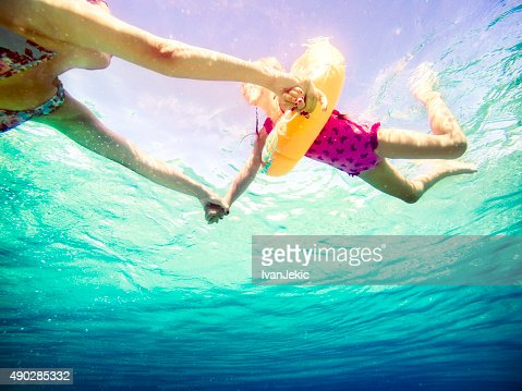 Underwater view of family swiming in sea and holding hands
