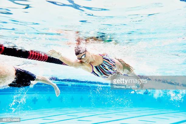 Underwater view of mature female athlete swimming during workout