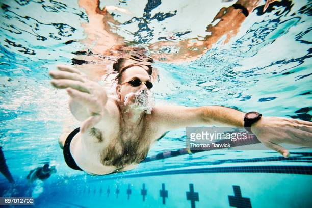 Underwater view of mature male athlete swimming butterfly during workout