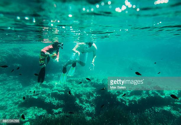 Underwater view of mature man and son sea snorkeling, Menorca, Balearic islands, Spain